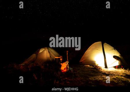 Abenteuer Romantik Nacht und Dämmerung in einem Zelt auf einer sternenklaren Nacht hoch in den Bergen vor der Morgendämmerung - Stockfoto