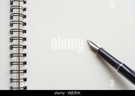 In der Nähe von Fountain Pen auf leeres Papier in Buch - Stockfoto