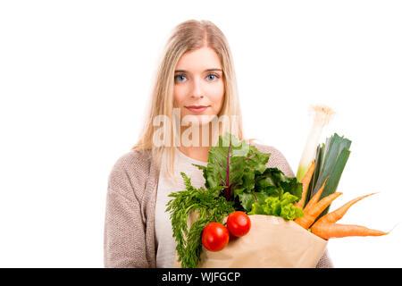 Schöne blonde Frau, die eine Tasche voller Gemüse, auf weißem Hintergrund - Stockfoto