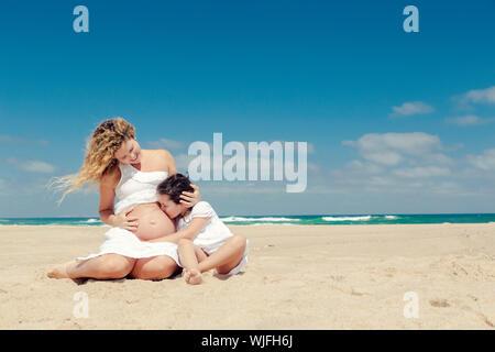 Schöne schwangere Frau und ihre kleine Tochter küssen Mama's Bauch - Stockfoto