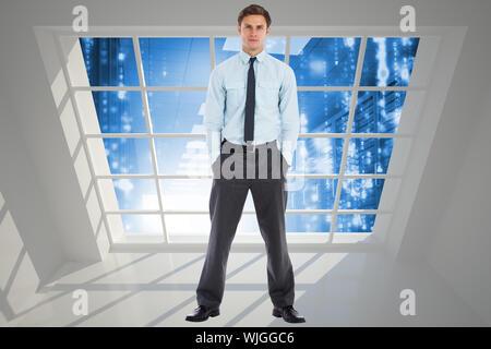 Ernsthafte Geschäftsmann stehend mit Händen in den Taschen gegen Server Flur durch das Fenster gesehen - Stockfoto