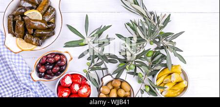 Traditionelle griechische Küche. Reis eingewickelt in Weinblätter. Dolma mit Zitrone, Gewürze, verschiedene eingelegte Oliven und Peperoni. Frische Zweige und hausgemachte Speisen - Stockfoto