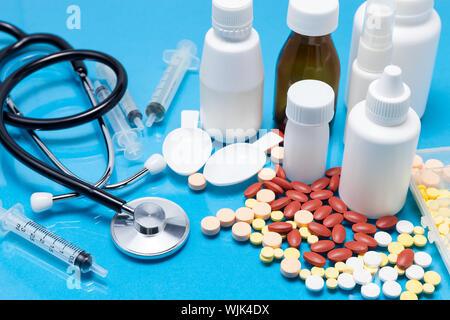 Hohe Betrachtungswinkel von Flaschen und Pillen mit Stethoskop auf blauem Hintergrund - Stockfoto