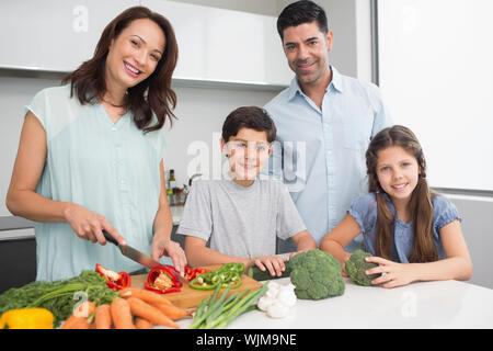 Lächelnde Frau mit zwei Kindern und mann Zerkleinern von Gemüse in der Küche zu Hause. - Stockfoto