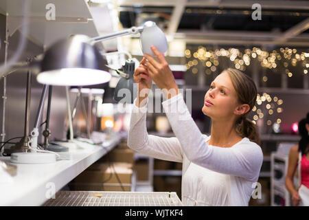 Hübsche, junge Frau, die Wahl der richtigen Lampe für ihre Wohnung in einem modernen Heimtextilien Shop (Farbe getönt Bild; flachen DOF) - Stockfoto