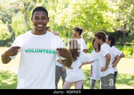 Portrait von Happy freiwillige Holding tshirt mit Freunden disucssing im Hintergrund - Stockfoto