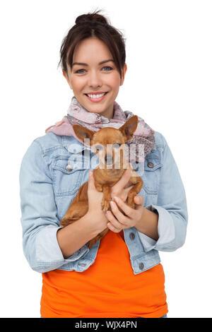 Porträt eines lächelnden jungen Frau mit Hund, die auf weißem Hintergrund - Stockfoto