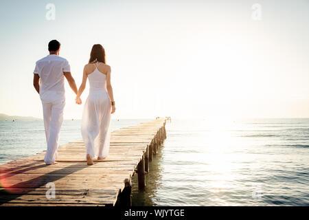 Ansicht der Rückseite des Paar hält Hände beim Gehen auf Holzsteg über Meer gegen Himmel während der sonnigen Tag - Stockfoto