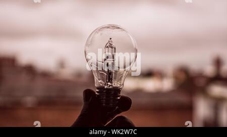 Nahaufnahme einer Hand, die Glühbirne gegen den Himmel - Stockfoto