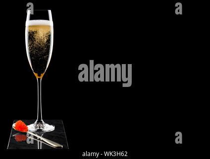 Elegante Glas Champagner gelb mit rotem Kaviar auf goldenen Löffel Kaviar auf Marmor Board auf Schwarz. - Stockfoto