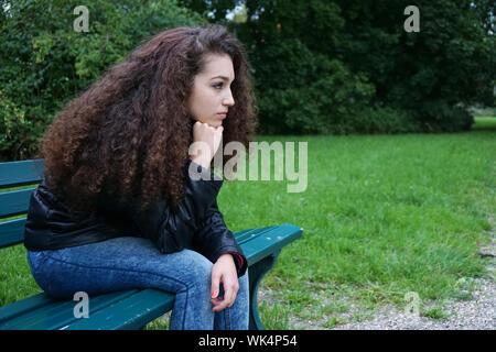 Seitenansicht der Nachdenkliche junge Frau sitzt auf der Bank im Park - Stockfoto