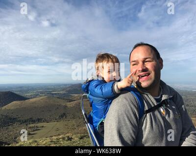 Vater Baby beim Stehen auf Berg gegen Sky - Stockfoto
