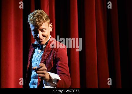 Kunst und Unterhaltung im Theater mit lustigen Mann arbeitet als Moderator, gegen rote Vorhänge und deutete auf Kamera - Stockfoto