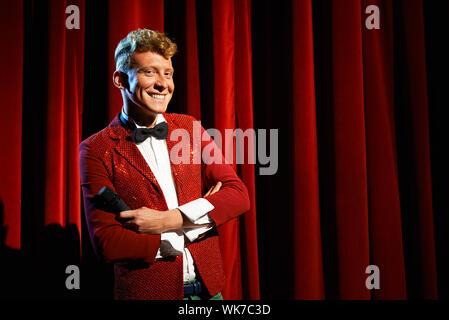 Kunst und Unterhaltung im Theater mit lustigen Mann arbeitet als Moderator, stehend mit verschränkten gegen rote Vorhänge mit Mikrofon - Stockfoto