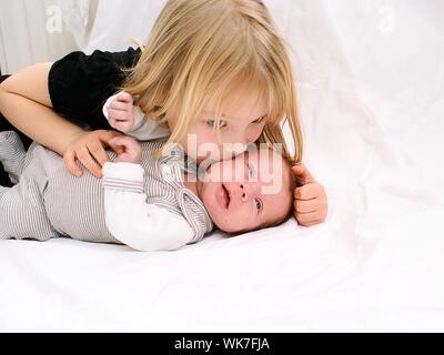 Schwester Küssen süß Bruder auf dem Bett zu Hause. - Stockfoto