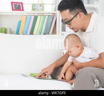 Asiatische Familie Lifestyle zu Hause. Vater und Kind Geschichte Buch auf Sofa. - Stockfoto