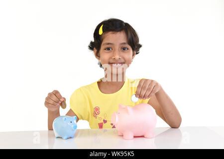 Mädchen, Münze in Sparschweine - Stockfoto