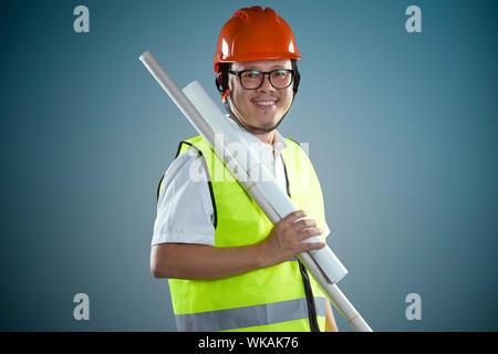 Jungen asiatischen Bauarbeiter in Helm und das gerollte Blueprints halten, auf blauem Hintergrund. - Stockfoto