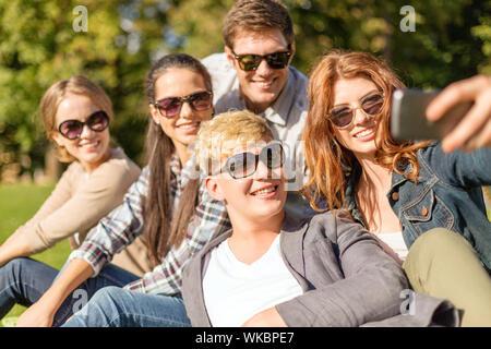 Sommer, Internet, social Networking, Technologie und Teenager Konzept - Gruppe von Teenagern, die Aufnahme von Fotos mit Smartphone-Kamera außerhalb - Stockfoto