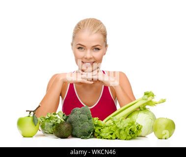 lächelnde sportliche Frau mit Bio-Lebensmitteln - Stockfoto