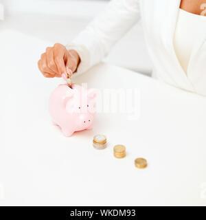 weibliche Hand Sparschwein Euromünzen Inbetriebnahme - Stockfoto