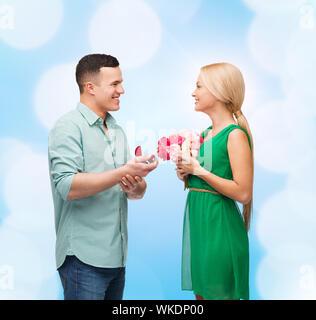 Glück, Urlaub, Feier und paar Konzept - lächelnde paar mit Blumenstrauß und Ring in einer box - Stockfoto