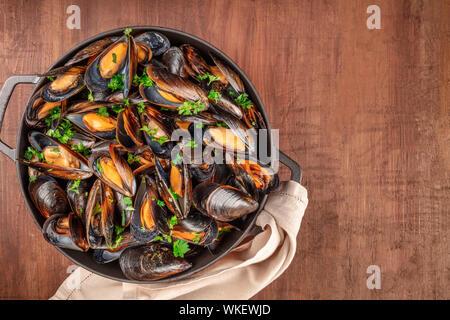 Marinara Muscheln, Moules Mariniere, in einem großen Topf kochen, Overhead shot auf einem dunklen Holzmöbeln im Landhausstil Hintergrund - Stockfoto