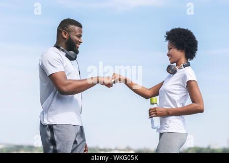 Afro Mann und Frau geben Fist Bump nach dem Joggen im Freien - Stockfoto