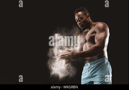 Junge bare-chested schwarzen Sportler mit Hilfe von Talkum auf seinen Händen - Stockfoto