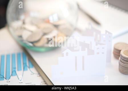 Hohe Betrachtungswinkel von Papier Haus mit Münzen und Diagrammen auf den Tisch - Stockfoto