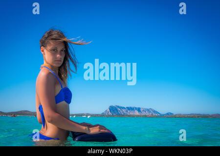 Porträt der jungen Frau im Meer gegen blauen Himmel - Stockfoto