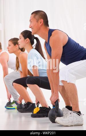 Heterogene Gruppe üben Kettlebell Übung im Crossfit gym - Stockfoto