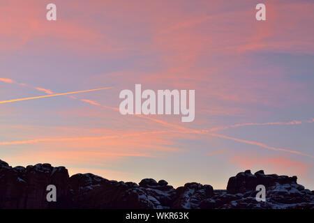 Sonnenuntergang Himmel mit Flugzeug Kondensstreifen über eine verschneite Landschaft, Arches National Park, Utah, USA - Stockfoto