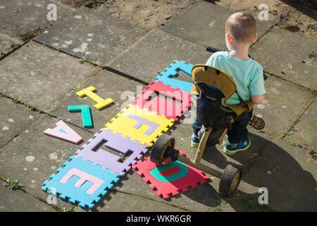 Hohe Betrachtungswinkel und der Boy, Dreirad von Text auf Pfad