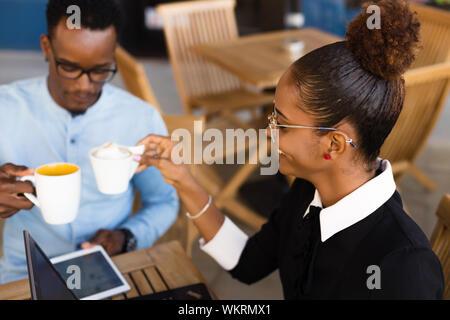 Schwarze Afrikanische amerikanische Kollegen tun digitale Teamarbeit rund um eine Tasse Kaffee - Stockfoto