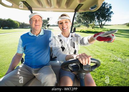 Viel Spaß paar im Golf buggy sitzen an einem sonnigen Tag auf dem Golfplatz - Stockfoto