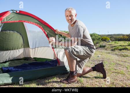 Happy Camper bis sein Zelt an einem sonnigen Tag einstellen - Stockfoto