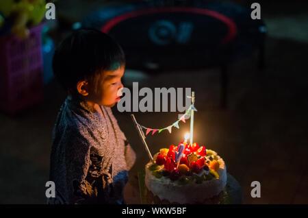 Jungen auf der Suche nach Kerzen auf der Torte in Dunkelkammer - Stockfoto
