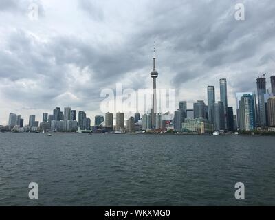 Cn Tower von Fluss gegen bewölkten Himmel in der Stadt Stockfoto
