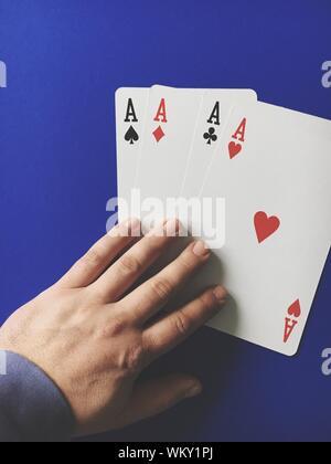 Hohe Betrachtungswinkel der Mann mit drei Assen Karten auf blauen Tabelle - Stockfoto