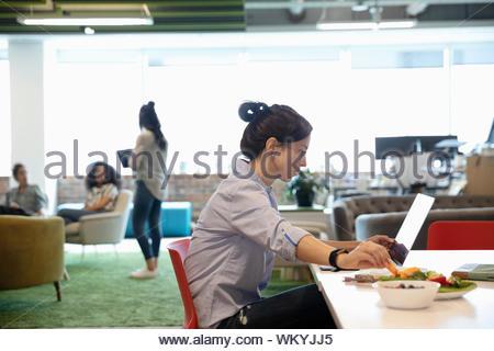 Geschäftsfrau, Essen und Arbeiten am Laptop im Großraumbüro - Stockfoto