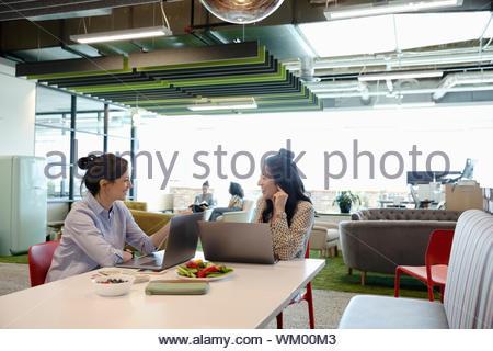 Unternehmerinnen Essen und arbeiten mit Laptops im Großraumbüro - Stockfoto