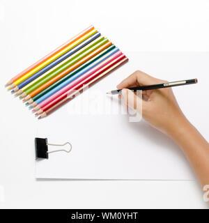 Asia Frau Rechte Hand mit schwarzer Stift und linke Hand mit bunten Bleistift auf leeres weißes Papier auf weißem Hintergrund - Stockfoto
