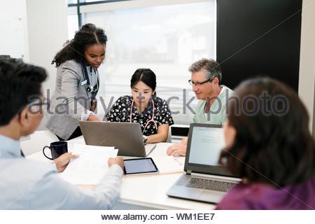 Ärzte, Krankenschwester und Administrator treffen, mit Laptop in der Klinik - Stockfoto