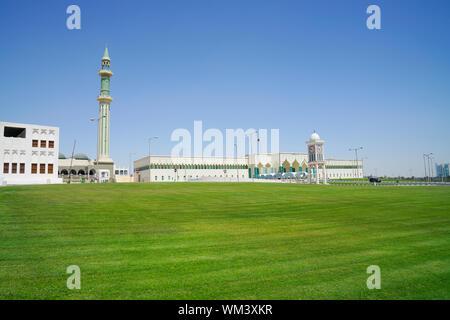Katar Parlament Gebäude gesetzt über weite grüne Wiese mit Glockenturm und die islamische Moschee auf der linken Seite. - Stockfoto