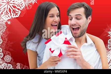Frau überraschend Freund mit Geschenk vor Weihnachten themed Schneeflocke frame - Stockfoto