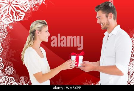 Junges Paar mit Geschenk vor Weihnachten themed Schneeflocke frame - Stockfoto