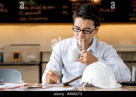 Mann hält Kaffee Tasse während der Arbeit auf dem Tisch im Cafe - Stockfoto