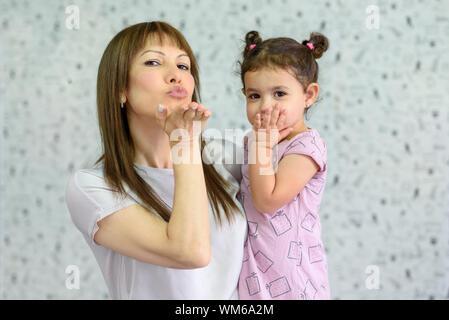 Mutter und Tochter lächeln in die Kamera blasen einen Kuss suchen, kleine Kinder verbringen viel Zeit am Wochenende gemeinsam mit jungen Oma, mit Freunden über das Internet zu kommunizieren. - Stockfoto