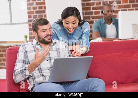 Junge casual Kollegen mit Laptop auf der Couch im Büro - Stockfoto